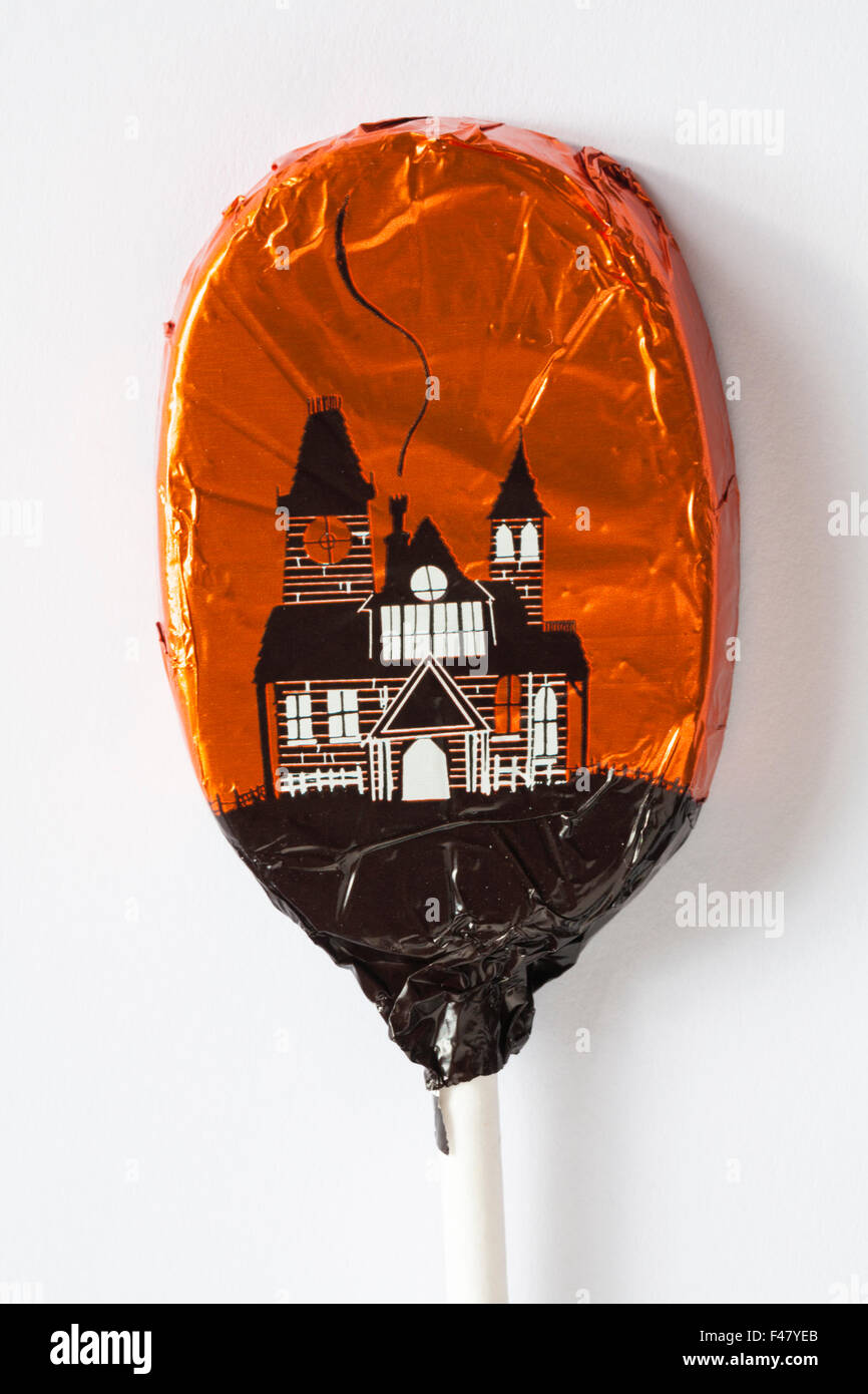 M&S spooky chocolate lolly foil wrapped with haunted castle design ready for Halloween set on white background - Stock Image