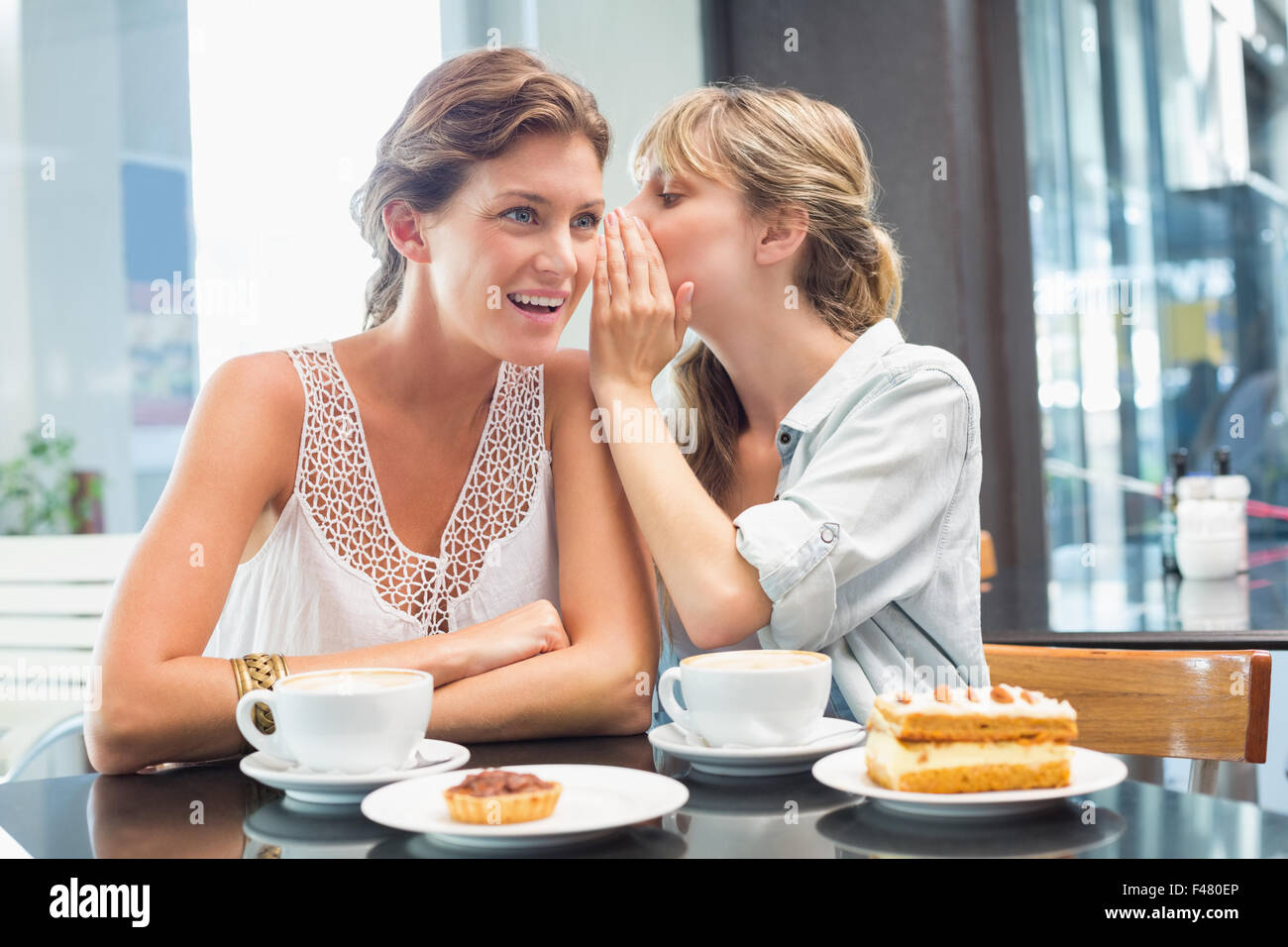 Beautiful women sitting and whispering secrets - Stock Image