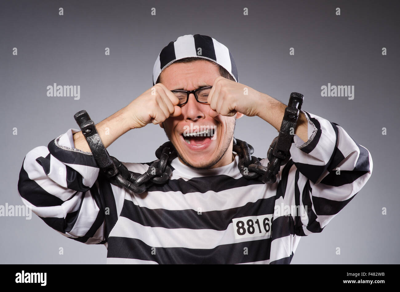Funny prisoner in chains isolated on gray - Stock Image