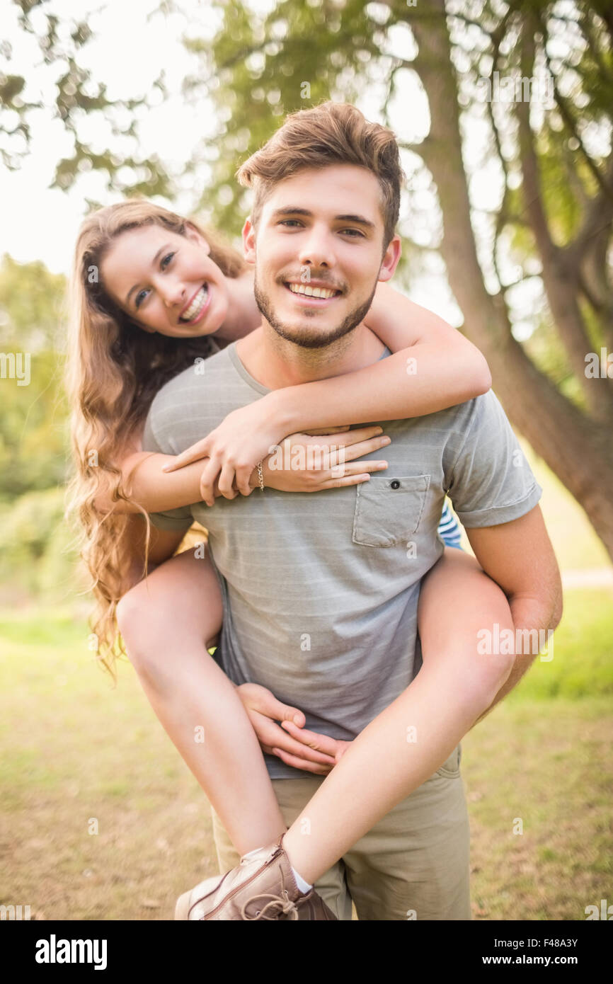 Handsome man giving piggy back to his girlfriend - Stock Image