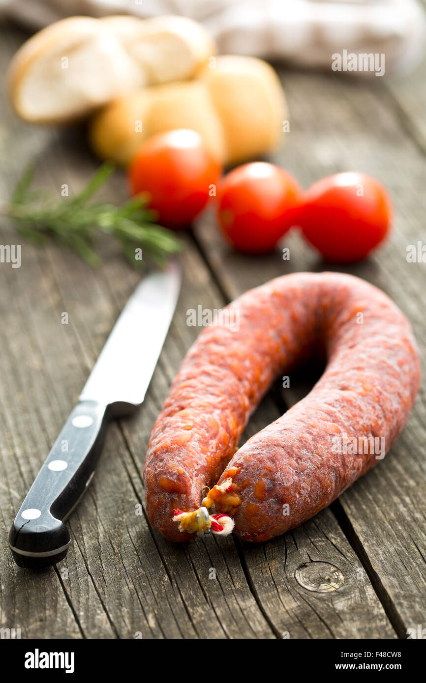 Chorizo sausage on old wooden table - Stock Image