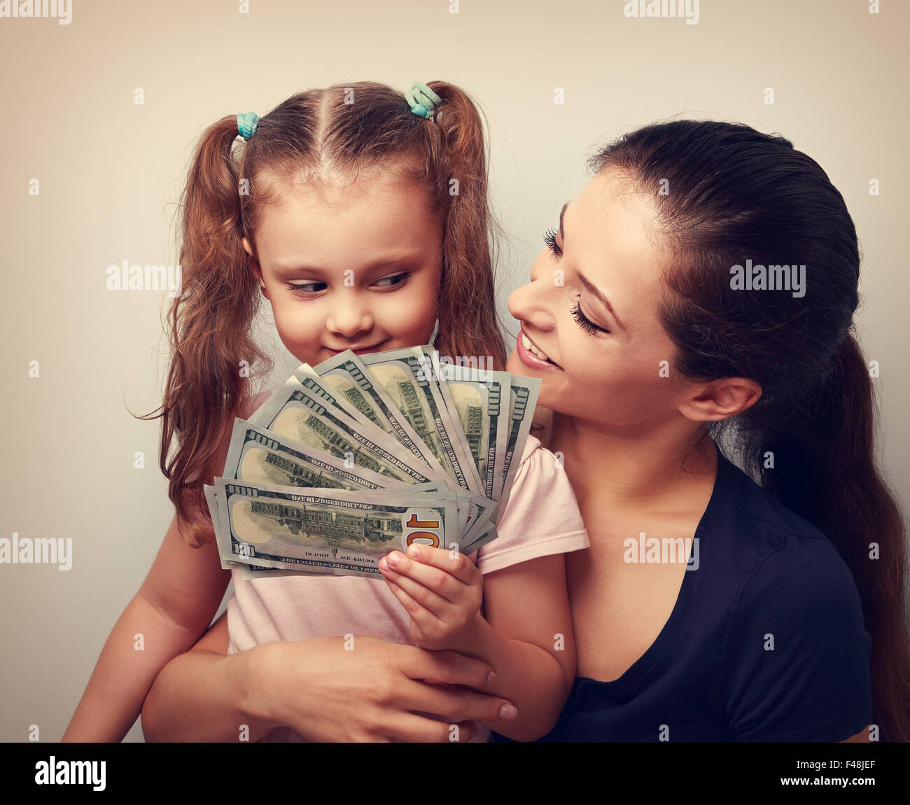 Happy casual family holding dollars and thinking how to spend the money. Vintage portrait Stock Photo