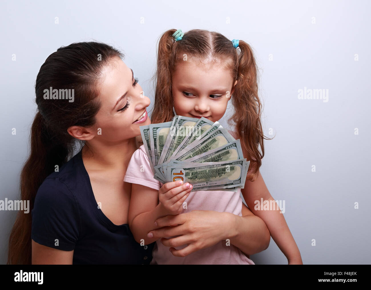 Happy casual family holding dollars and thinking how to spend the money. Portrait Stock Photo