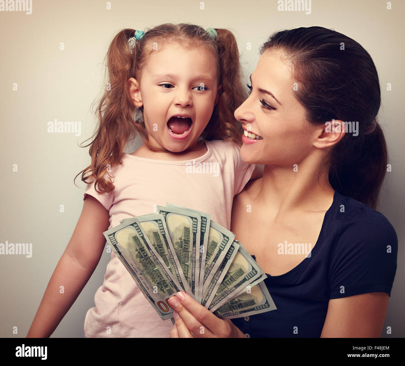 Happy smiling family holding dollars and thinking how to spend the money. Vintage closeup portrait - Stock Image