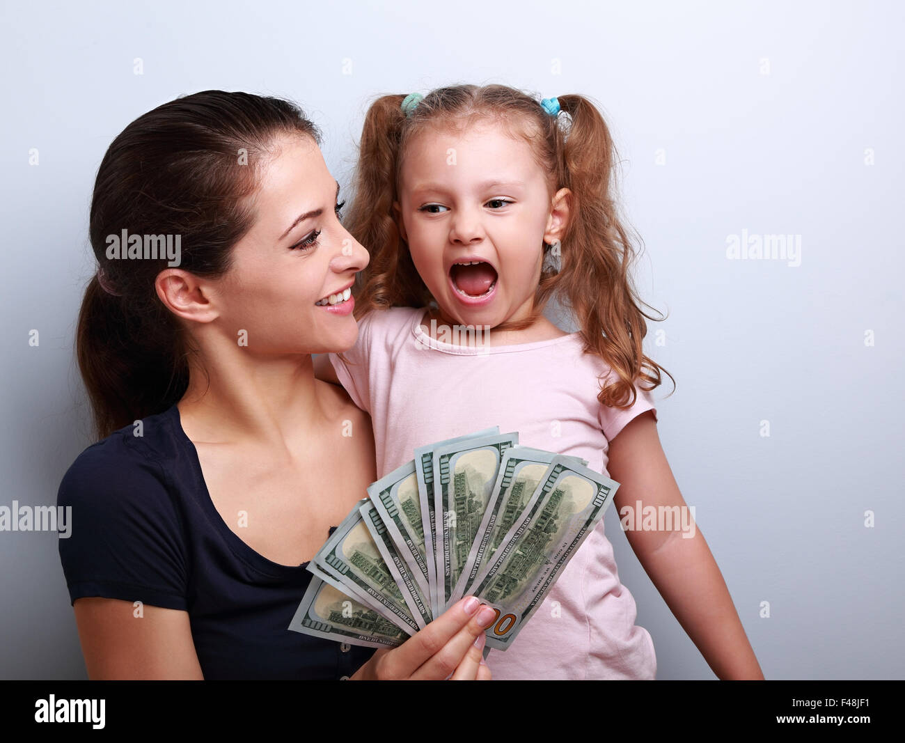 Happy smiling family holding dollars and thinking how to spend the money. Portrait on blue background with empty - Stock Image