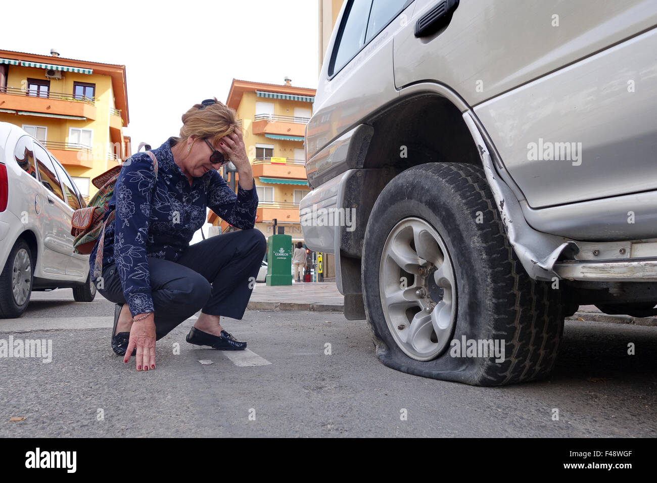 Woman female driver motorist with flat punctured car tyre puncture Stock Photo