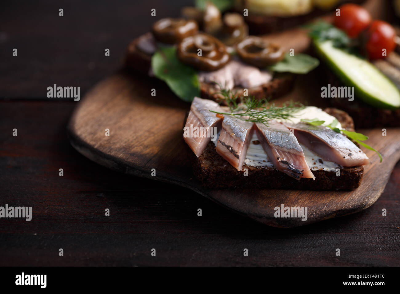 Variety of open sandwiches of buttered dense, dark rye bread with different toppings. Danish smorrebrods on wooden - Stock Image
