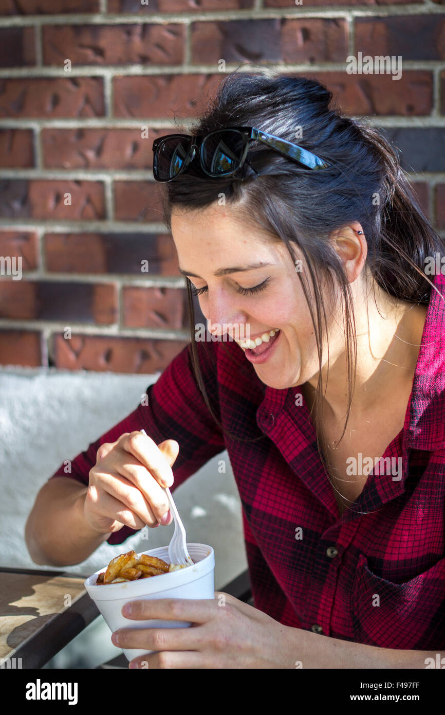 Happy young women eating poutine quebec meal fast food outdoor in daytime - Stock Image