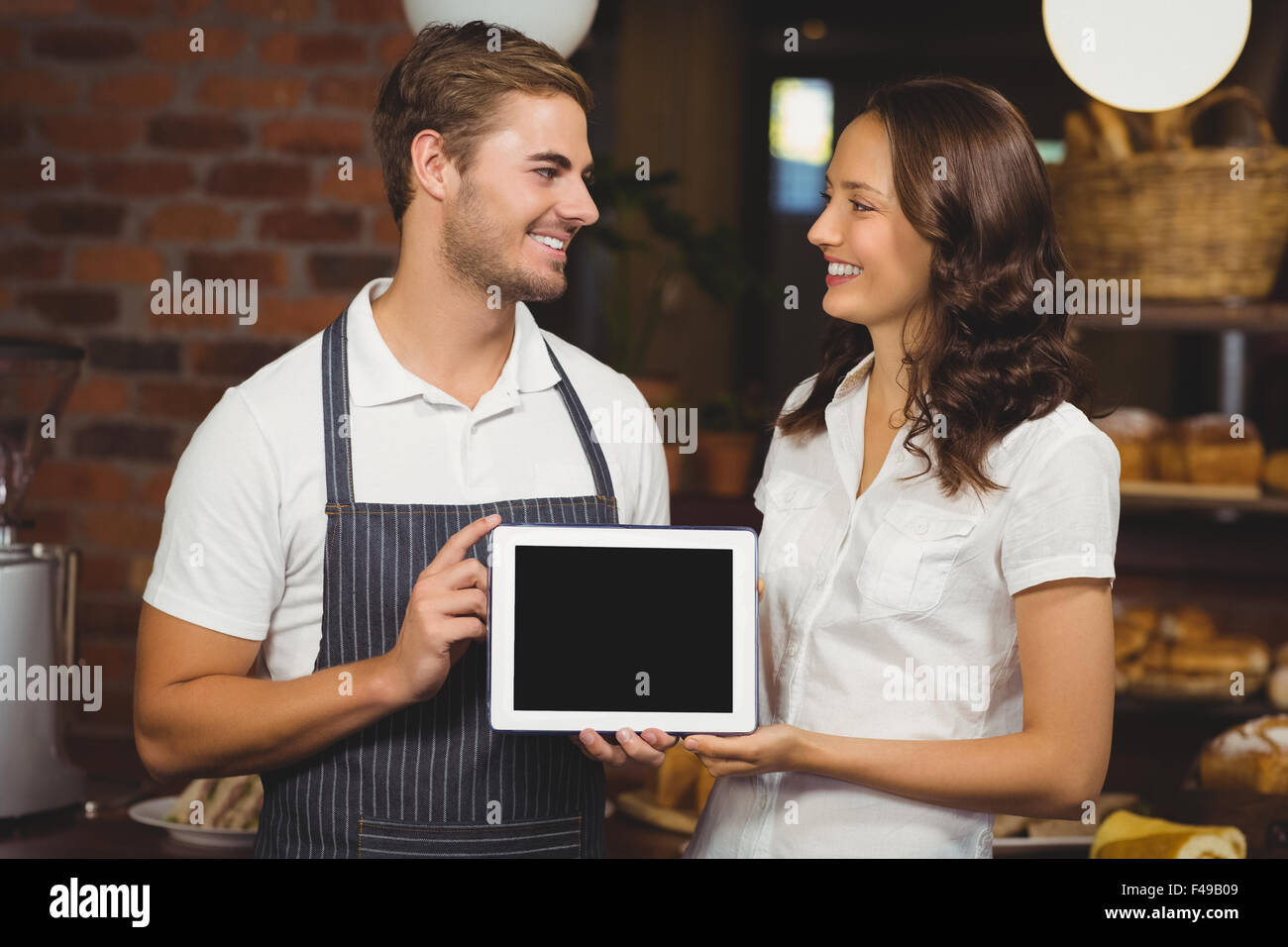 Smiling co-workers showing a tablet - Stock Image