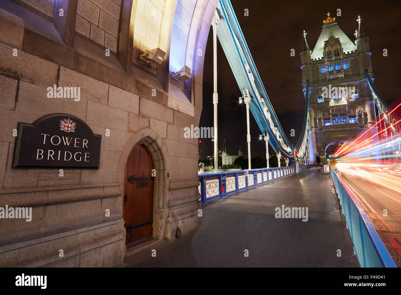 Tower bridge in London illuminated at night with car passing lights - Stock Image