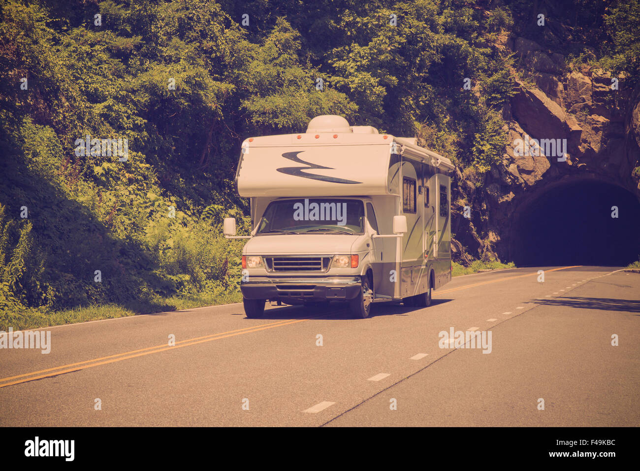 Vintage style image of recreational vehicle camper driving on highway - Stock Image