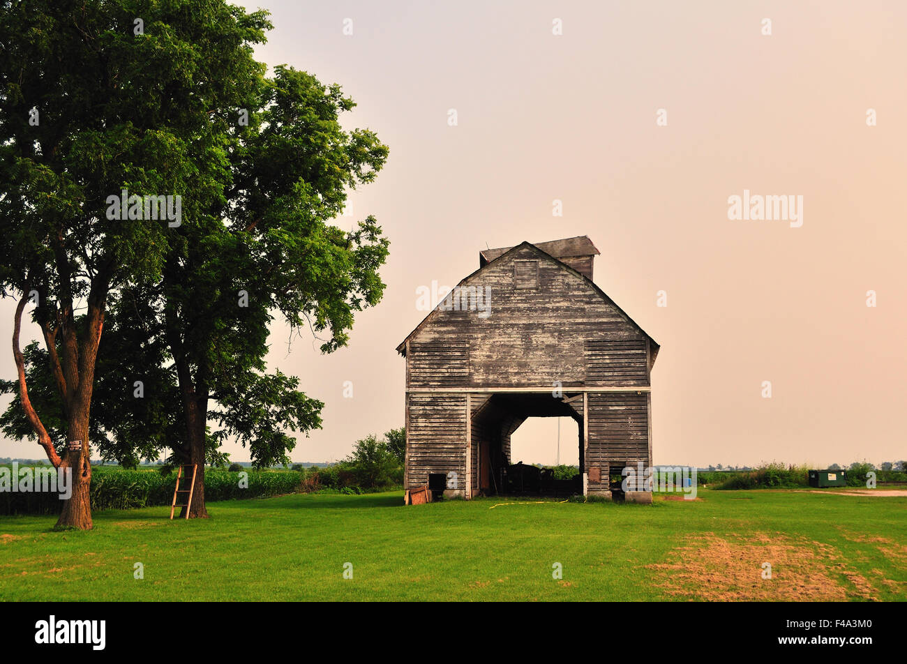 A veteran, time-weathered barn in need of paint and repair on a farm near Burlington, Illinois, USA. - Stock Image