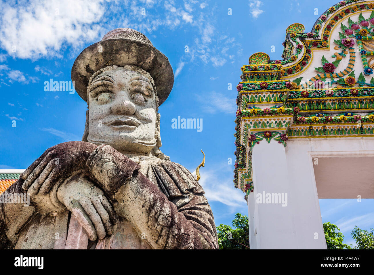 Thailand, Bangkok, Wat Po, warrier statue with top hat guarding a gate to the buddhist temple - Stock Image