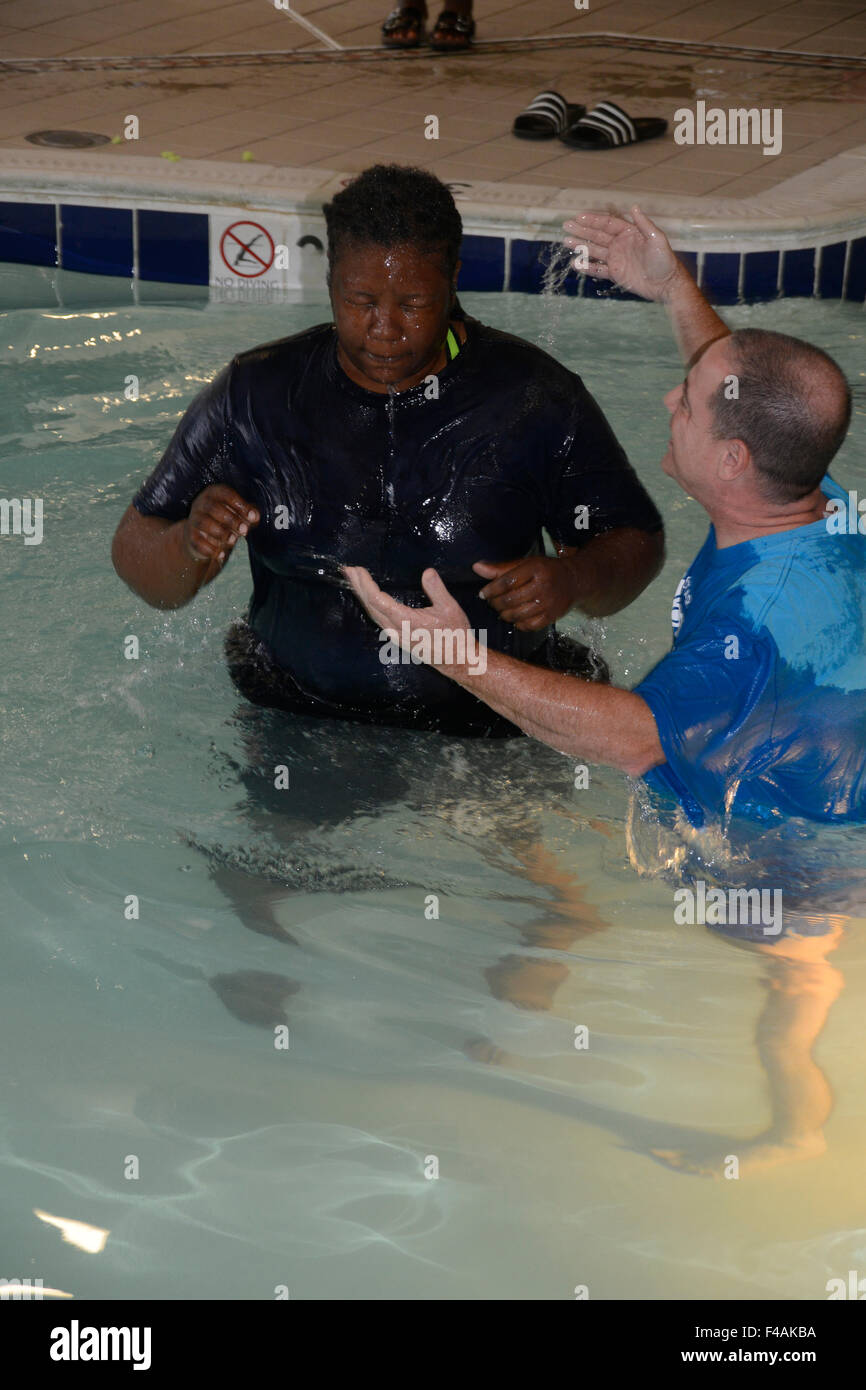 Woman is congratulated by a minister after being baptizedd during a baptism ceremony - Stock Image