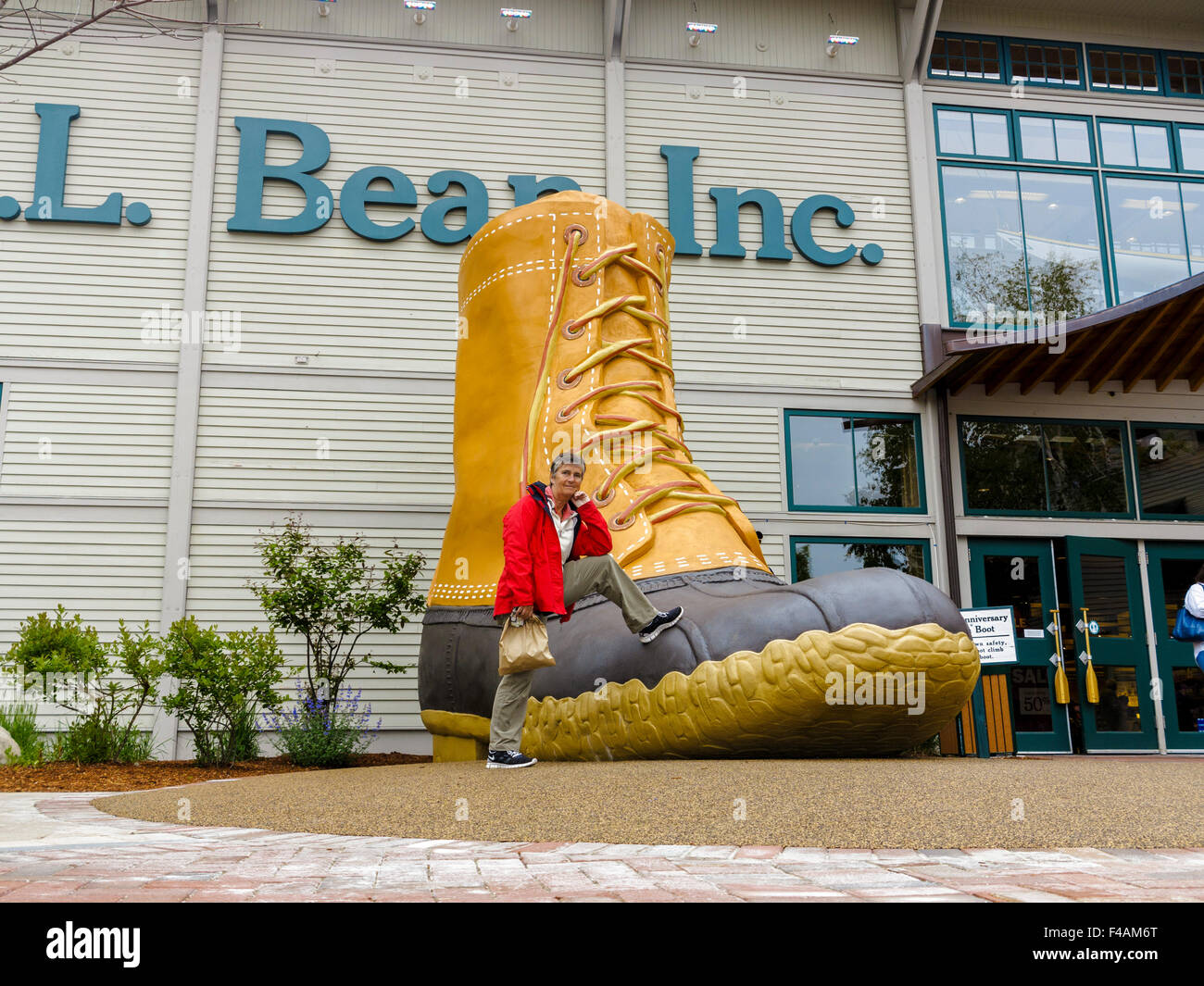 Woman leaning on the huge L.L. bean iconic boot outside their store in Freeport, Maine - Stock Image