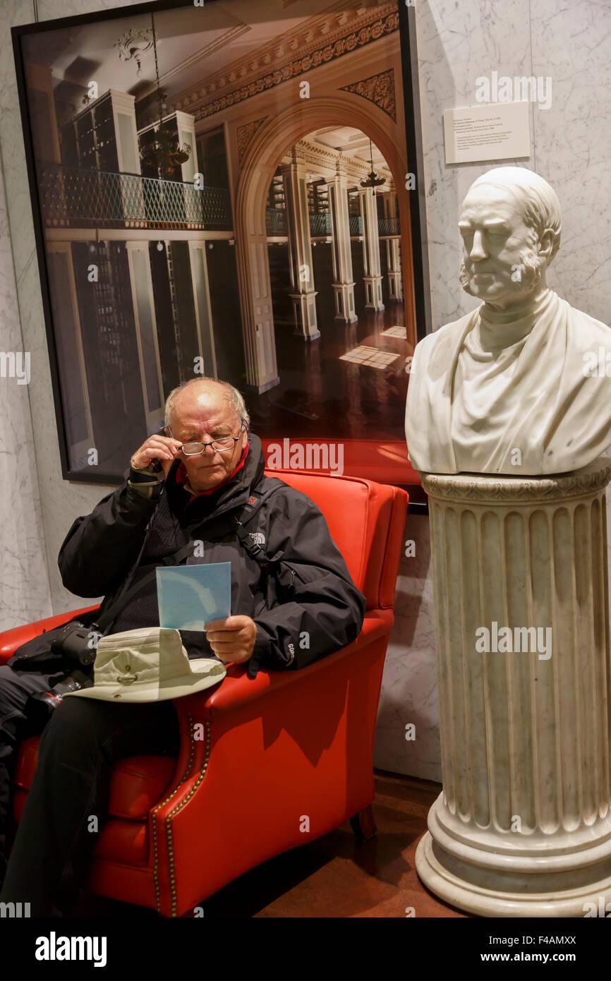 Senior man wearing spectacles sitting reading in the Boston Athenaeum - Stock Image