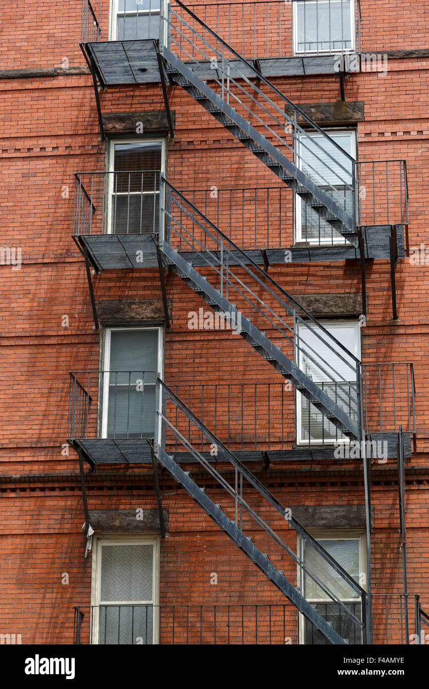 Traditional metal fire escape on the side of a brick building - Stock Image