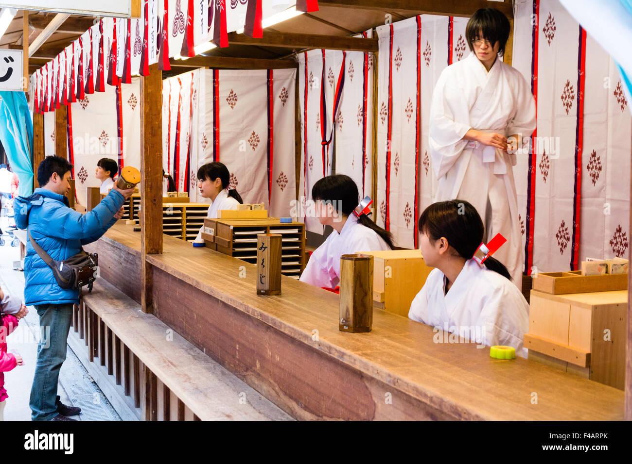 Japan, Nishinomiya shrine, New year Day, Shogatsu. Woman buying omikuji fortune papers from Miko, shrine maiden, - Stock Image