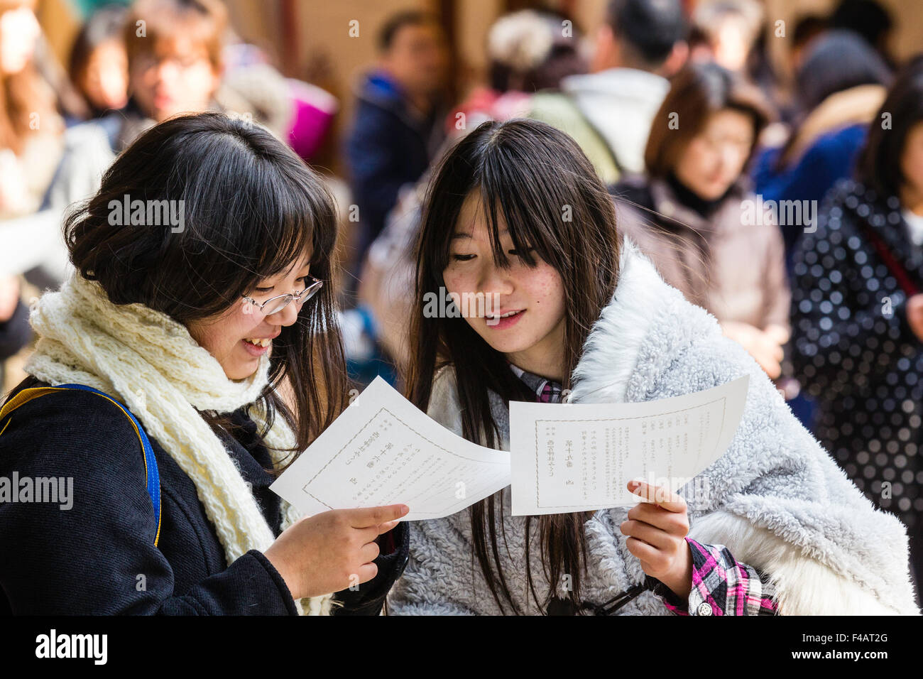 Nishinomiya Shinto shrine. Two young women, both holding omikuji, fortune paper, but both discussing one paper, - Stock Image