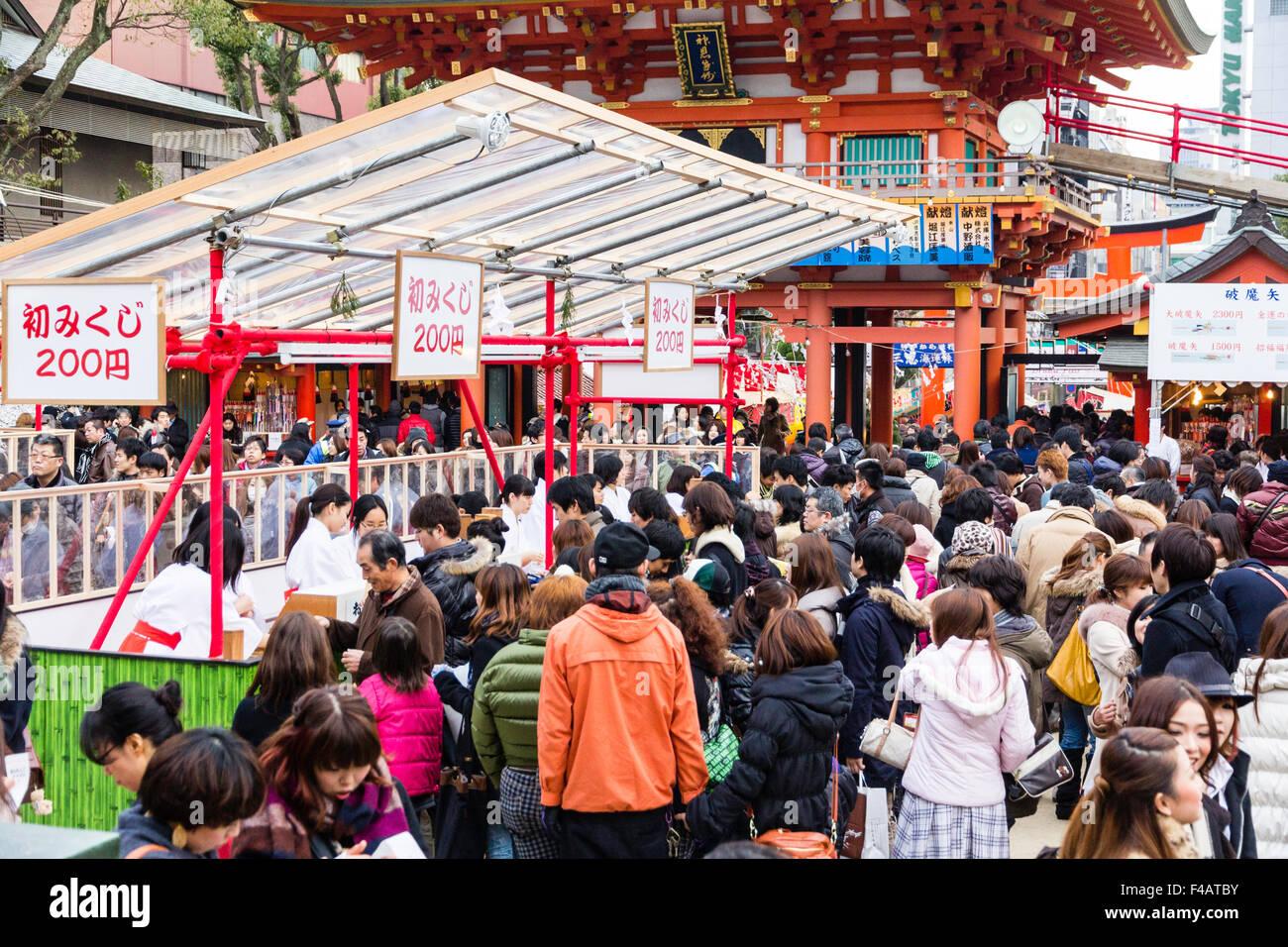 Ikuta shrine, Kobe. New Year. Crowds filling the shrine buying fortune papers, omikuji, from Miko, shrine maidens - Stock Image