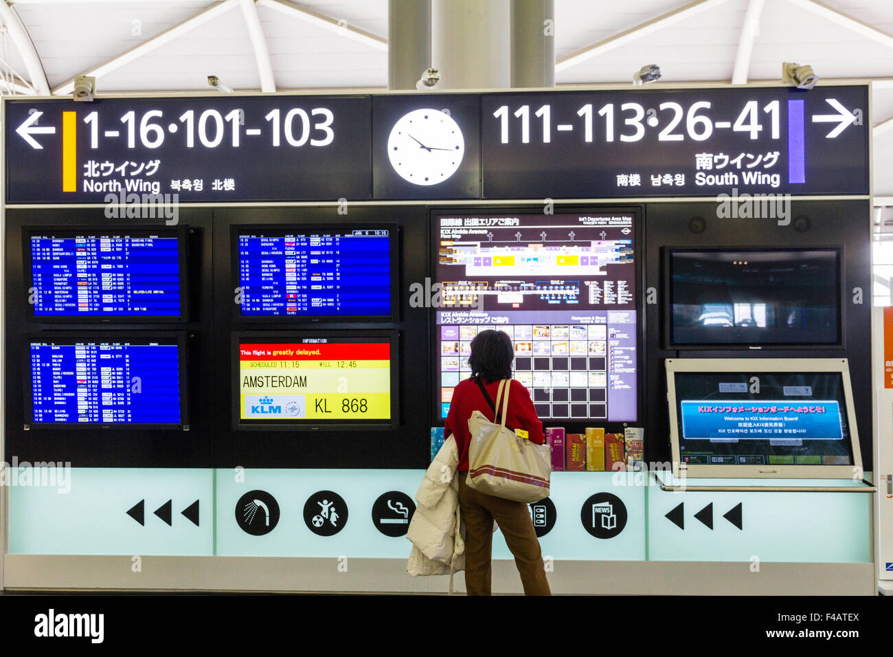 Kansai Airport, Osaka, Japan. Flight infromation in main departure lounge with passenger checking flights - Stock Image