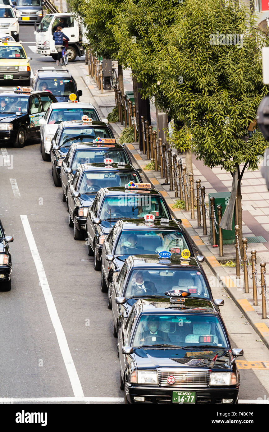 Japan, Osaka, Umeda. Overhead view looking down along at a lone line of Japanese taxis waiting on a main street. - Stock Image