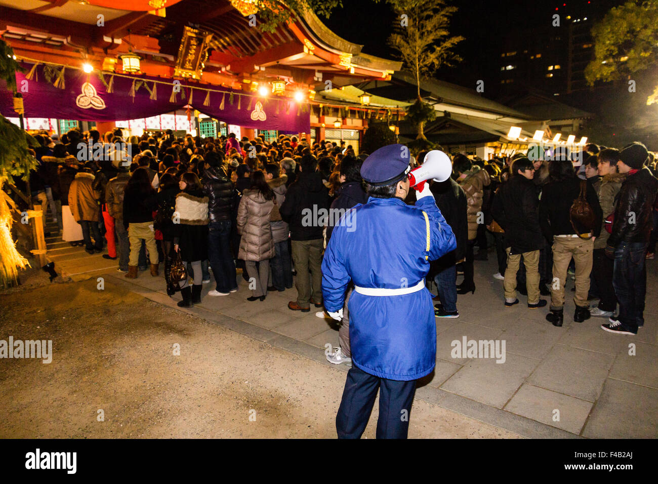 New Year's eve, Nishinomiya shrine, midnight. Security man using loud hailer in front of queue of hundreds of - Stock Image