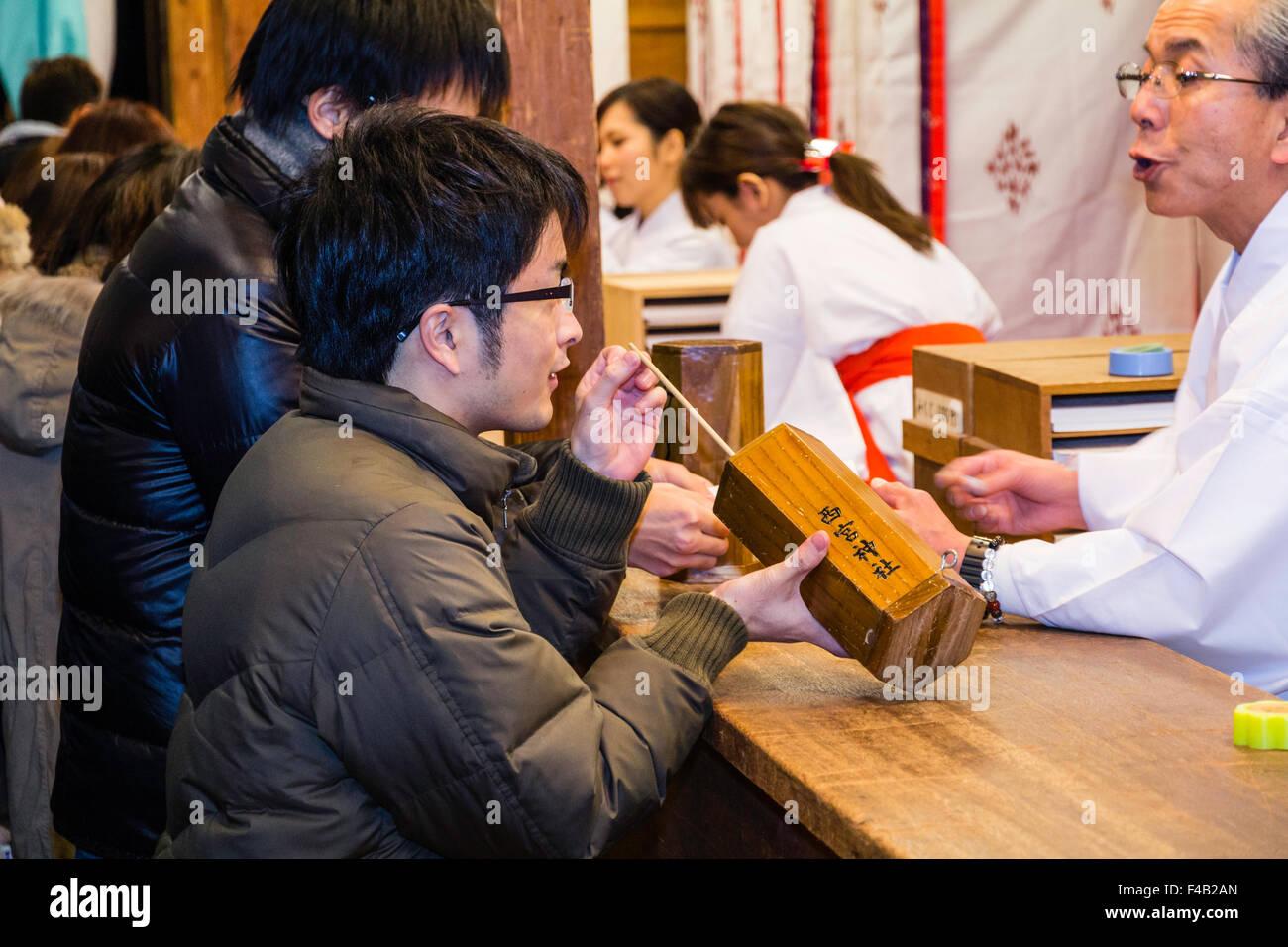 Japan, Nishinomiya shrine, New year Day, Shogatsu. Couple buying omikuji fortune papers from busy shrine office, - Stock Image
