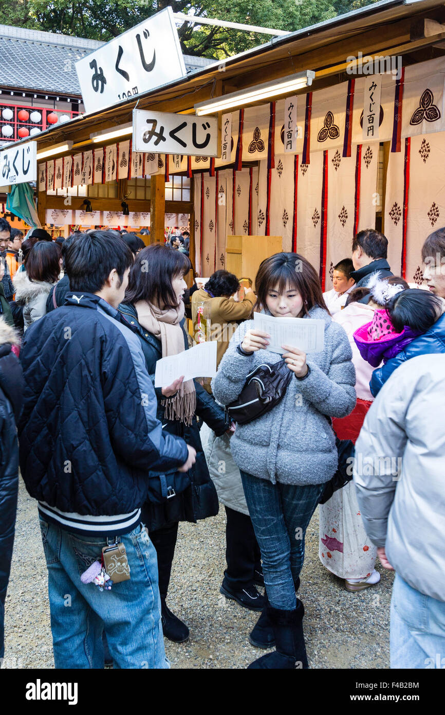 Japan, Nishinomiya shrine, New year's Day, Shogatsu. Two young women and young man standing together, reading - Stock Image