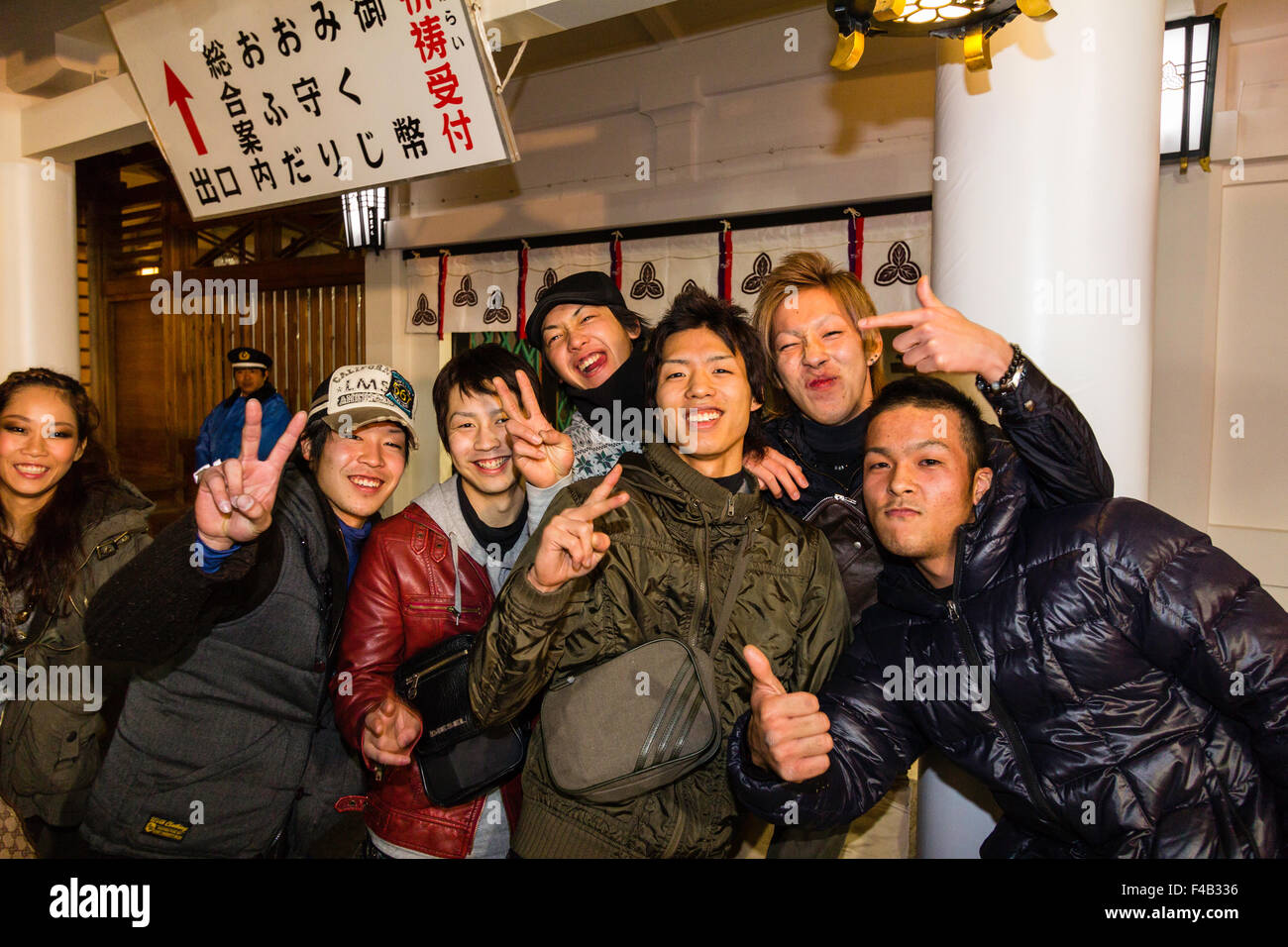 Japan, Nishinomiya Shinto shrine, new year, midnight. Group of people in front of viewer smiling and giving the - Stock Image