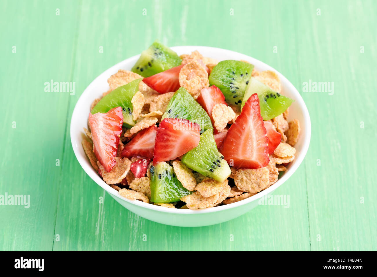 Corn flakes with fresh strawberry and kiwi slices in bowl on green table Stock Photo