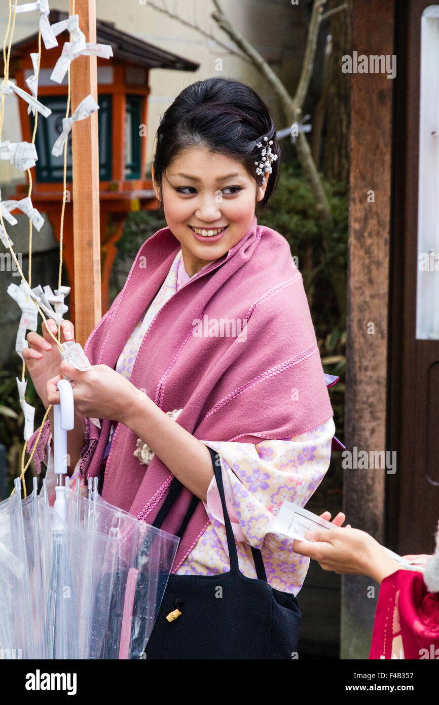 Kyoto, Yasaka shrine, New Year, Shogatsu. Young woman wearing traditional happi coat reading omikuji, good fortune - Stock Image