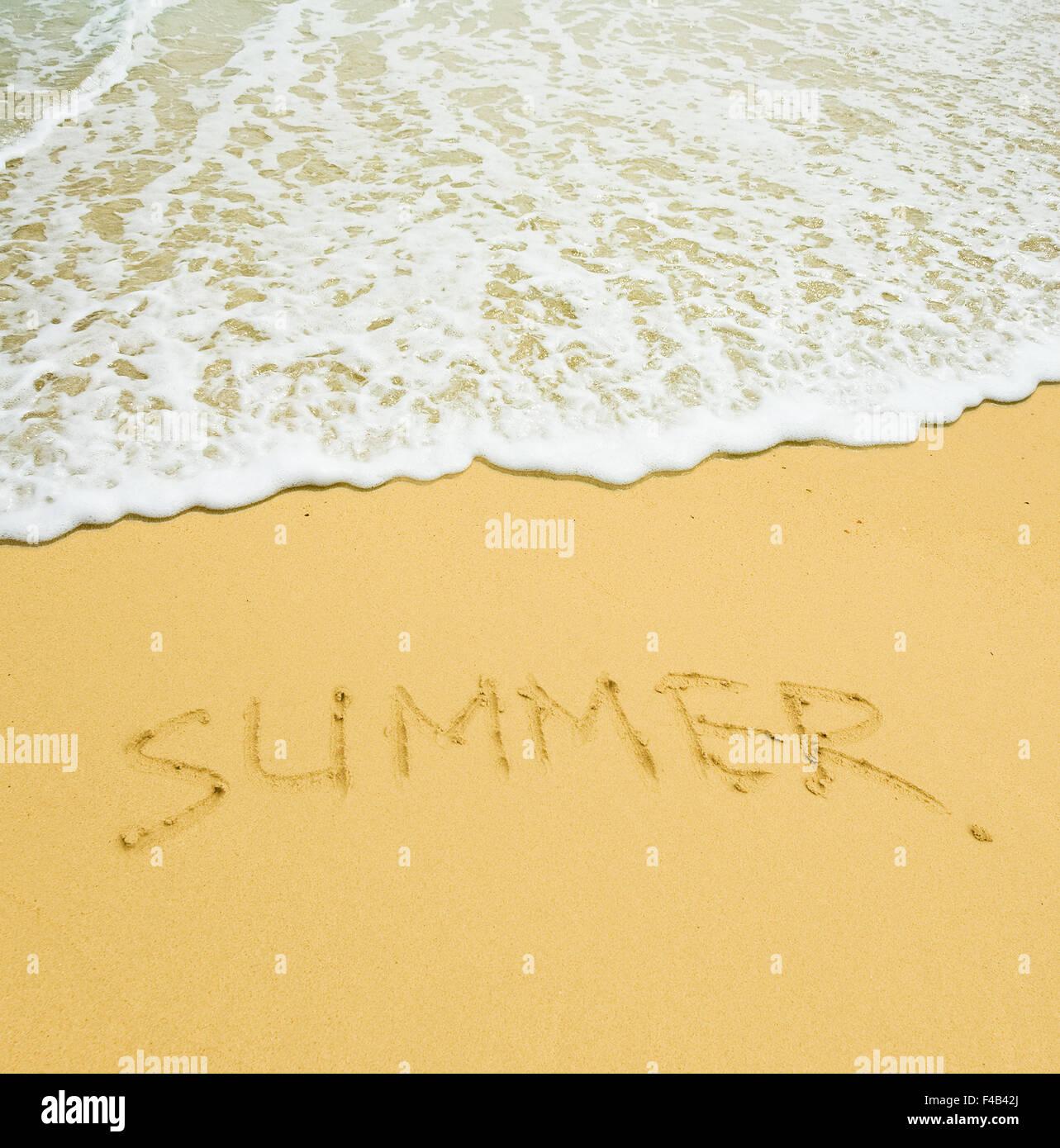 summer written in a sandy tropical beach - Stock Image