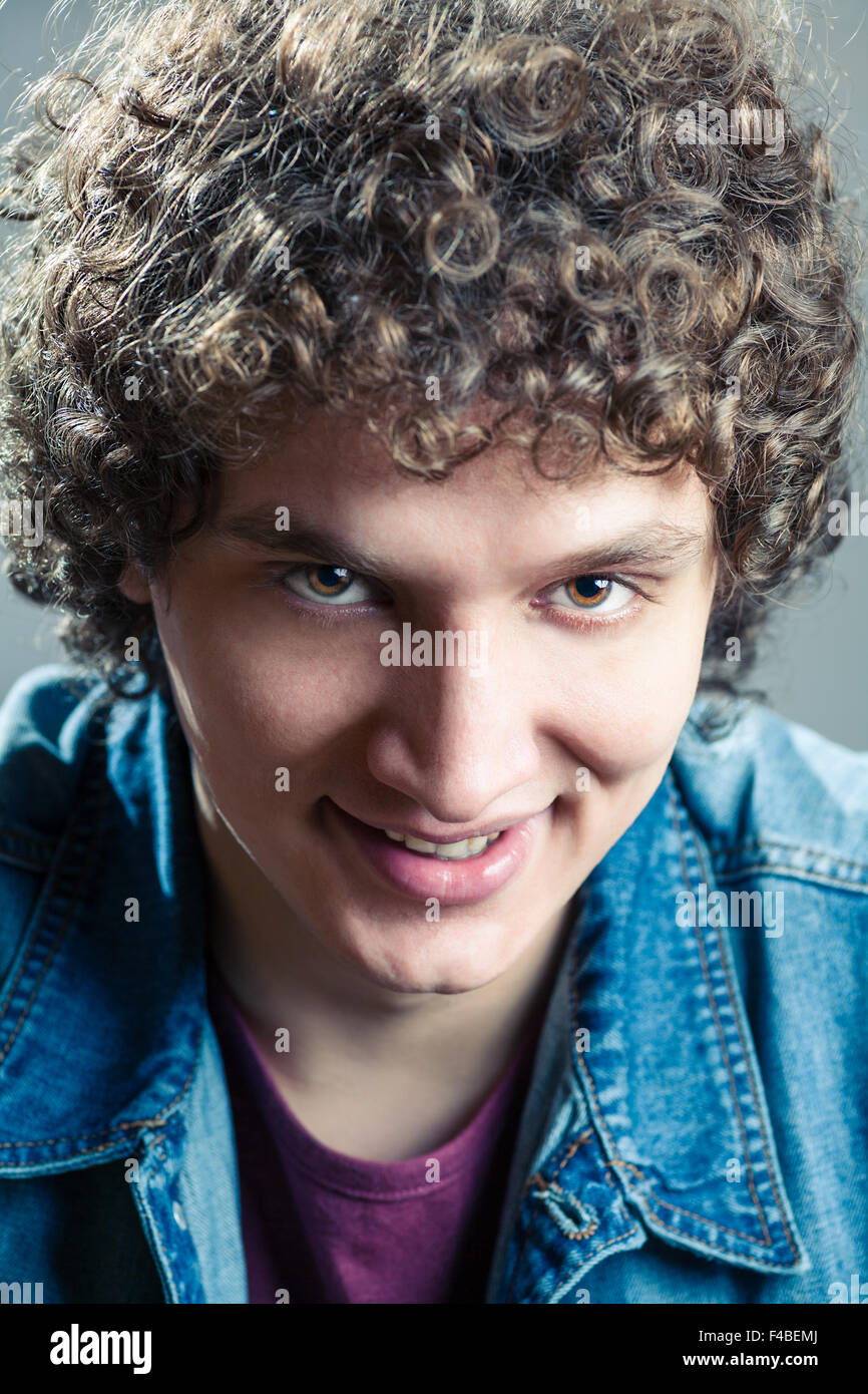 Smiling curly-haired man closeup - Stock Image