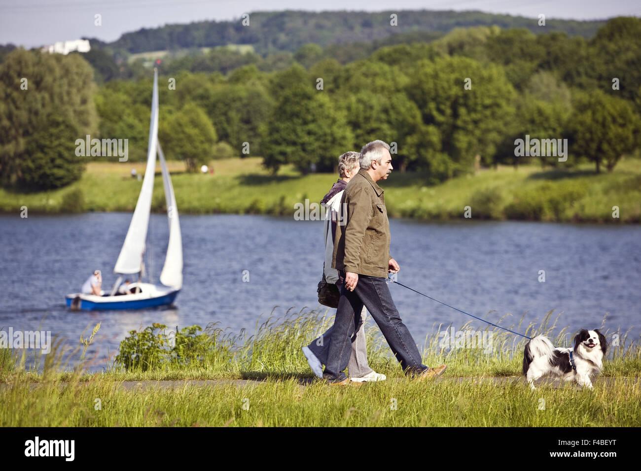 Walkers and sailboat, Lake Kemnade, Germany. - Stock Image
