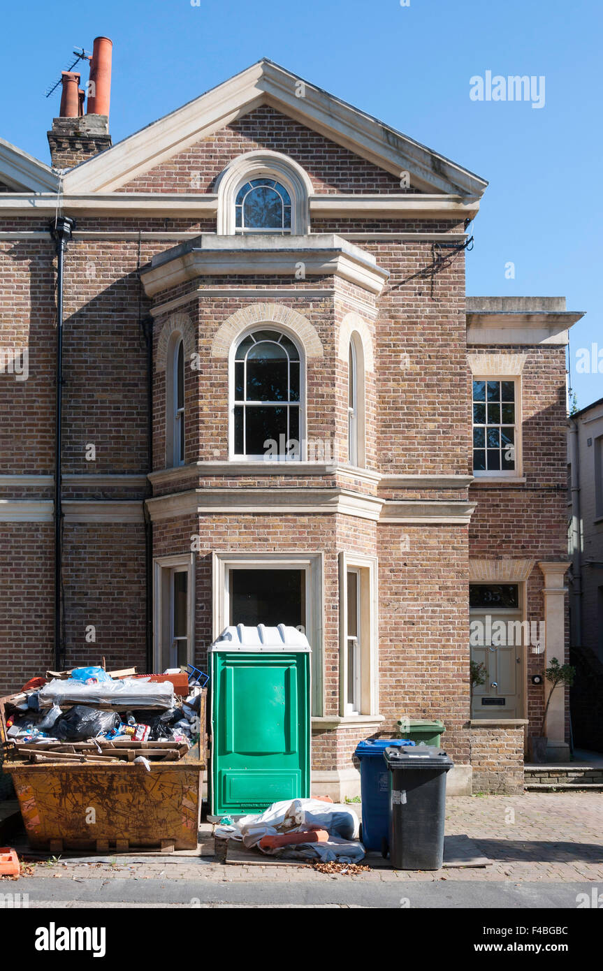 House being renovated with skip outside, High Street, Datchet, Berkshire, England, United Kingdom - Stock Image