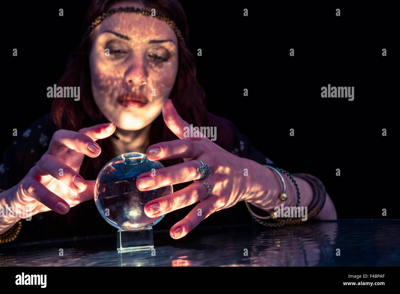 Serious female fortune teller with crystal ball - Stock Image
