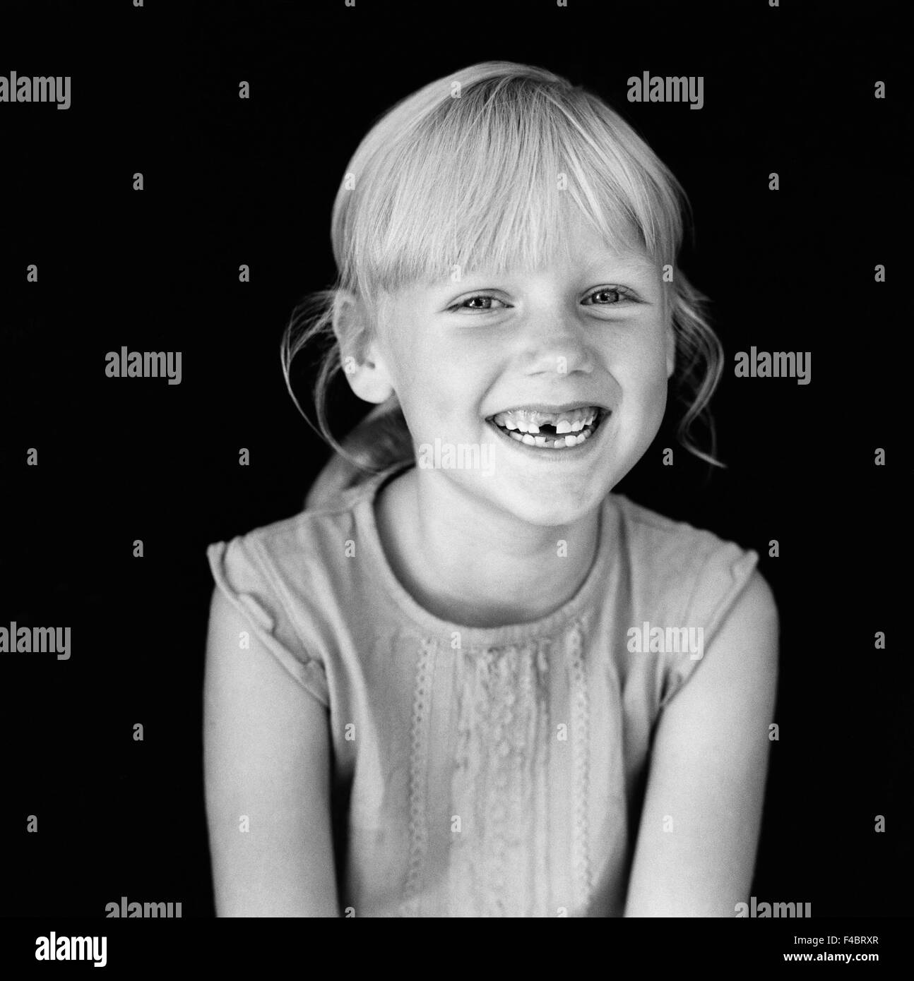 black and white blonde children only girls happy indoors one person only optimism portrait positive smiling tooth - Stock Image