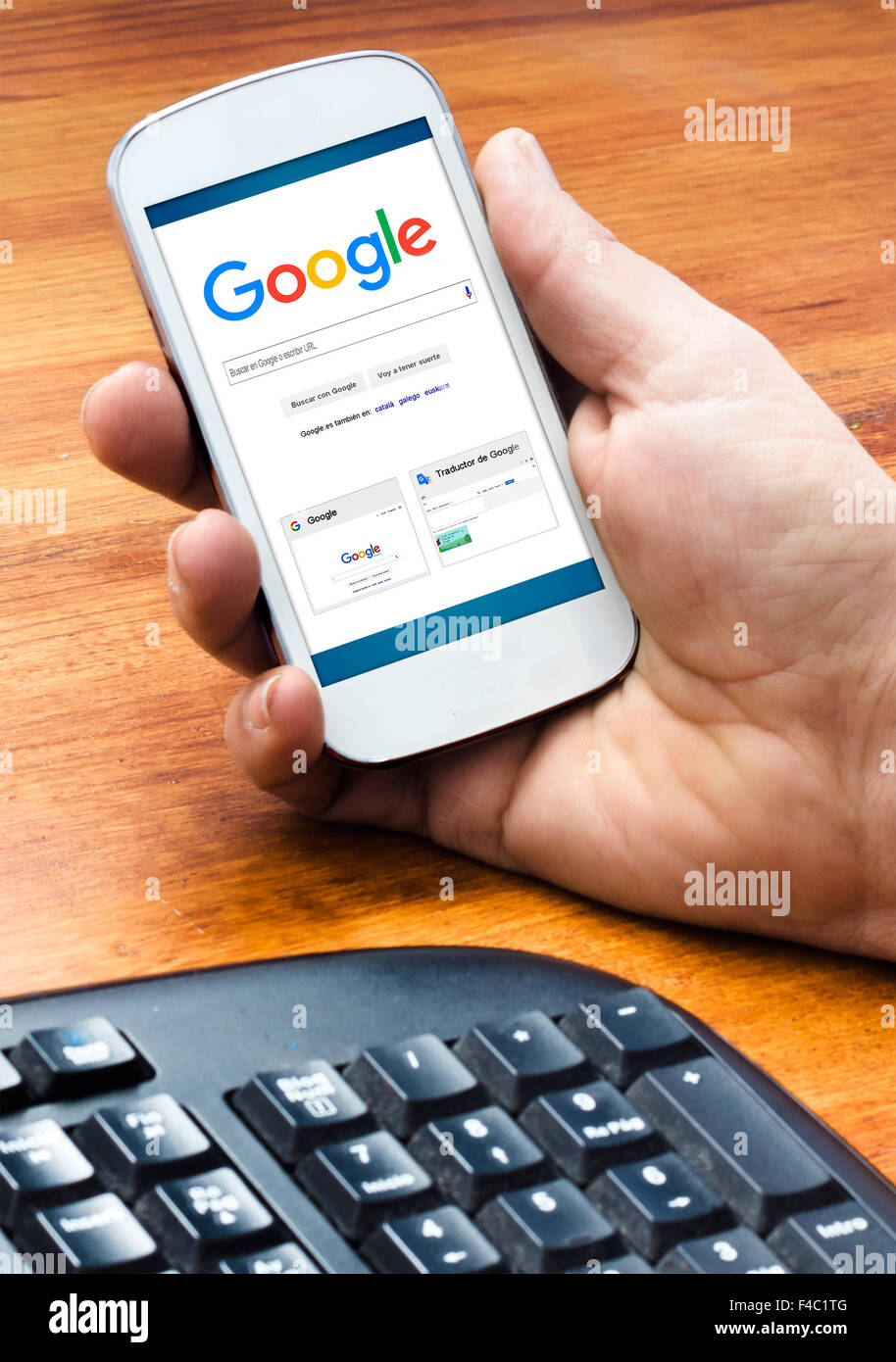Barcelona, Spain- September 4, 2015: Male hand holding on smartphone with Google Web Search homepage on the screen - Stock Image