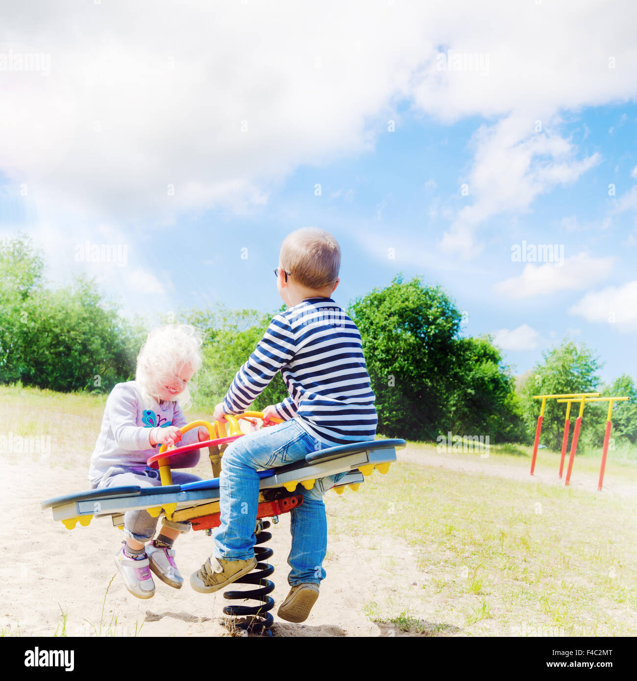 Boy and girl swinging on a swing - Stock Image