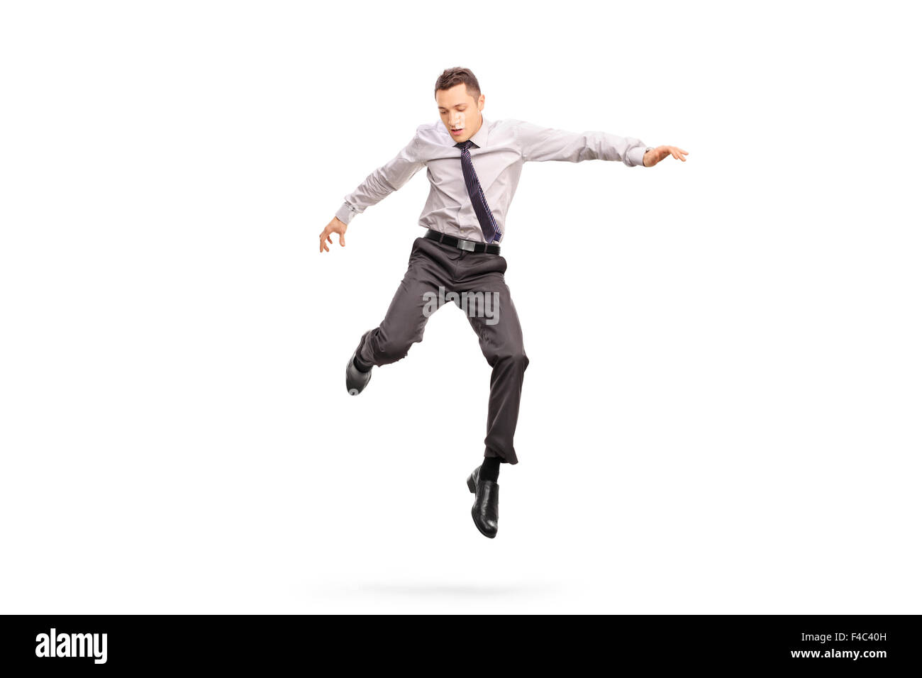 Full length portrait of a young businessman jumping in the air and looking down isolated on white background - Stock Image