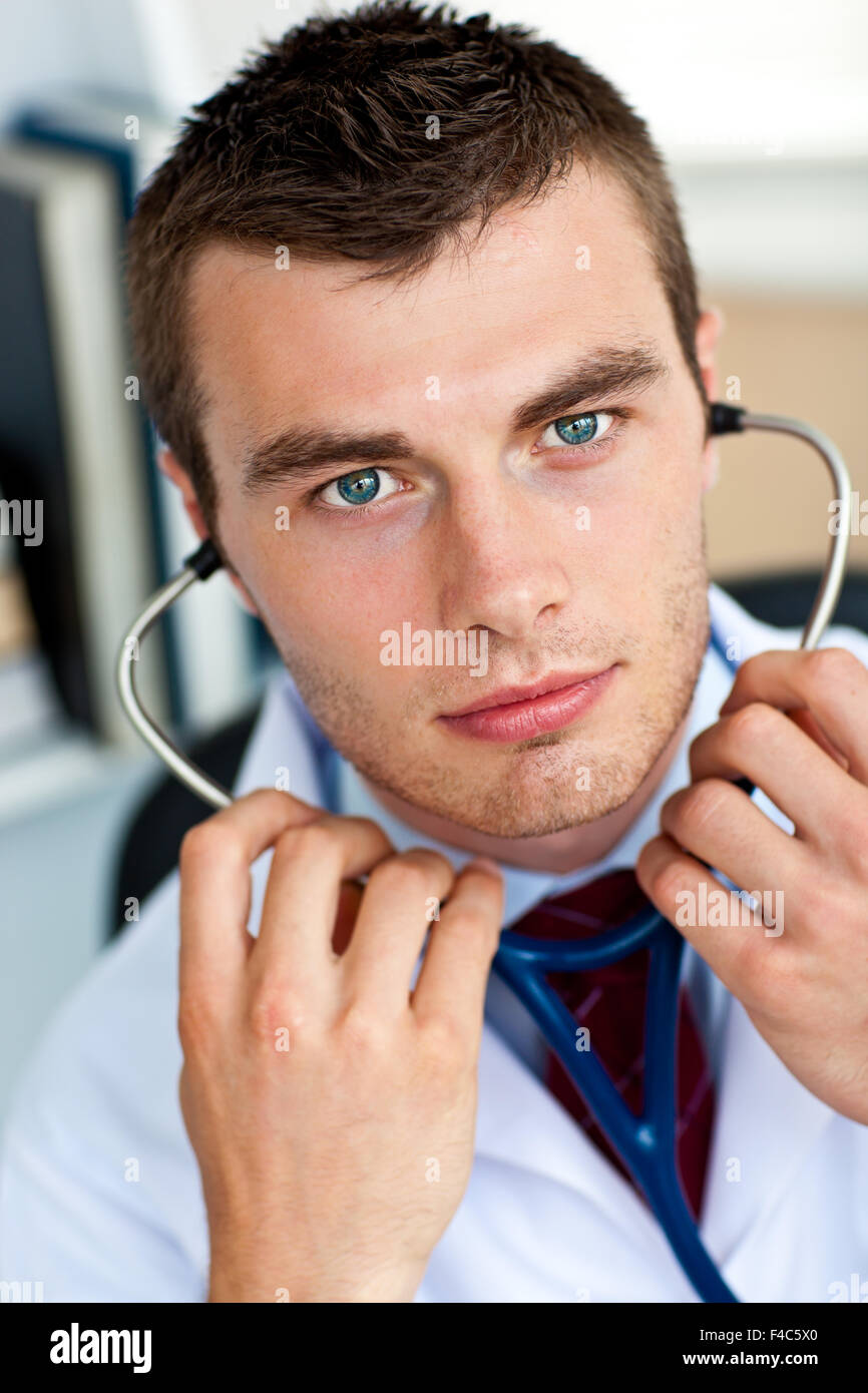 Confident male doctor holding a stethoscope in his office - Stock Image