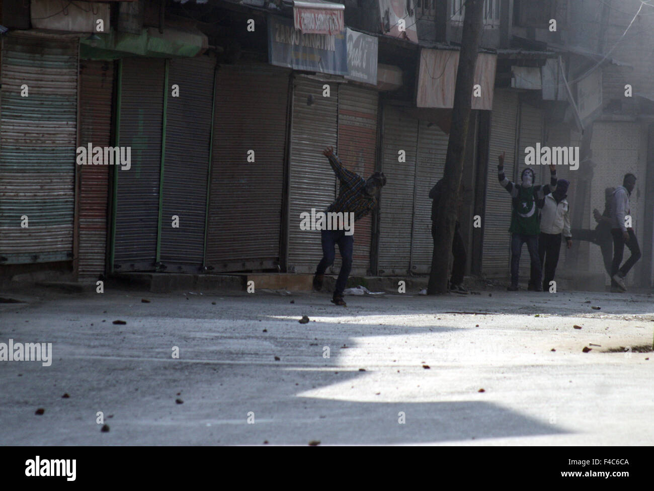 Srinagar, Indian Administered Kashmir:16 October. kashmiri Muslim protestors throw stones (unseen) during clashes - Stock Image