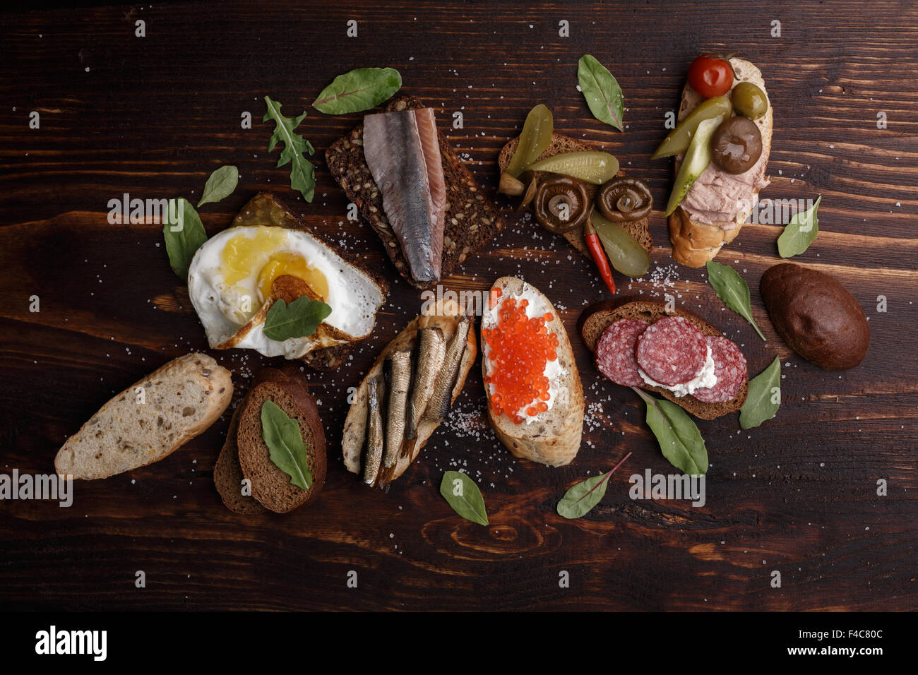 Variety of open sandwiches from wholegrain baguette and rye bread with different toppings over dark wooden backdrop. - Stock Image