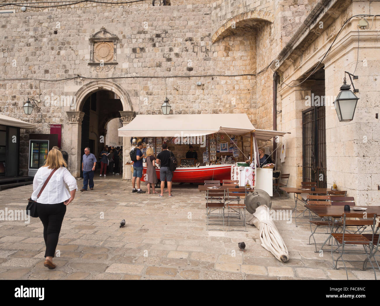 Souvenirs for sale in a boat shaped stall in the old harbour of Dubrovnik Croatia under the fortification walls - Stock Image