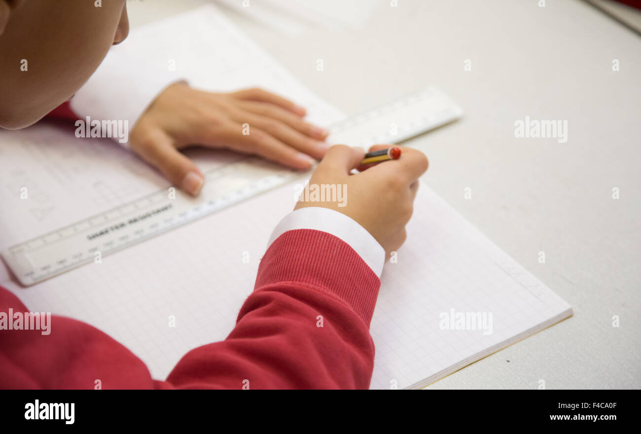 A typical UK primary school classroom with a pupil drawing a line with a ruler - Stock Image