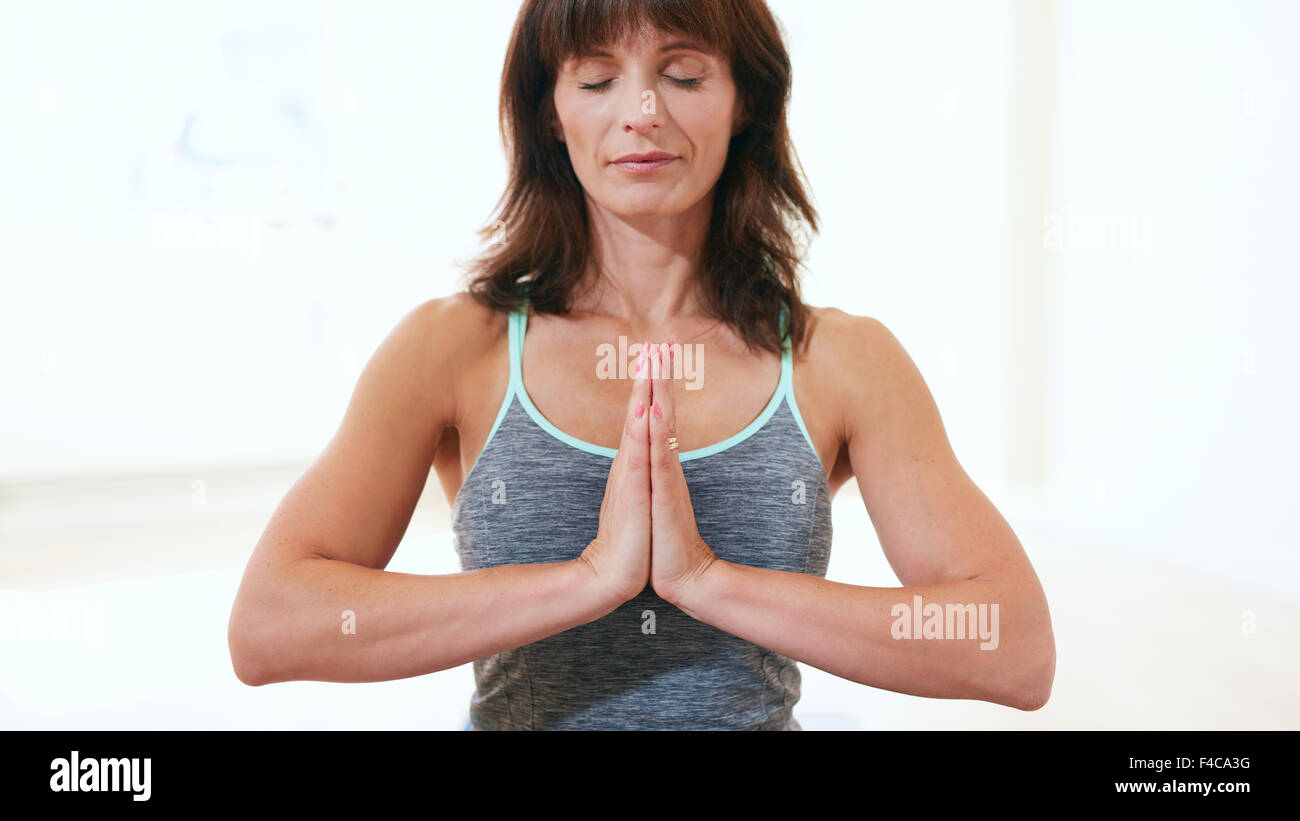 Portrait of healthy woman practicing meditation yoga. Mature caucasian female sitting at the gym with her hands - Stock Image