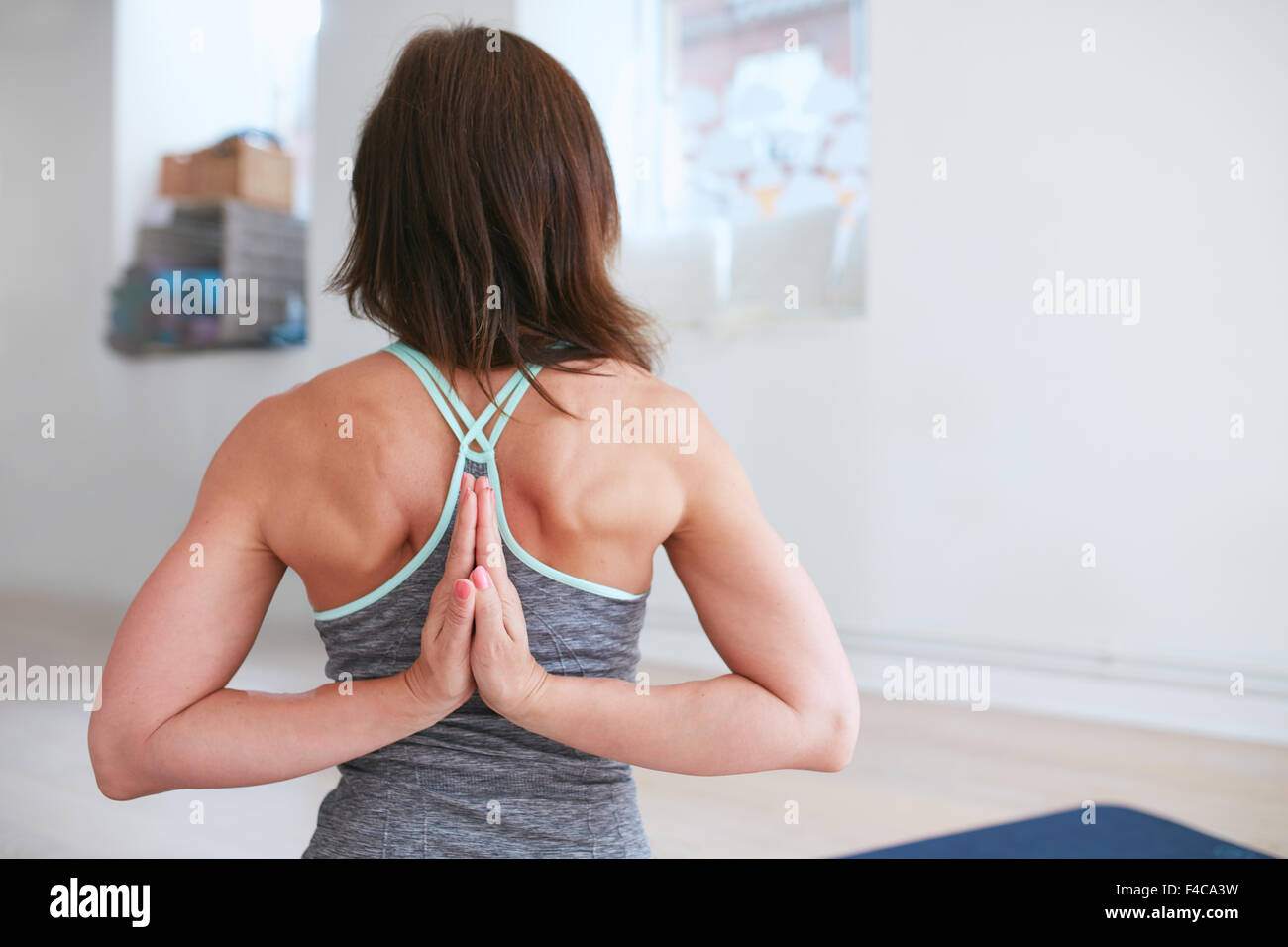 Rear view of fitness woman doing yoga  in reverse prayer pose. Pashchima Namaskarasana performed by a female at - Stock Image