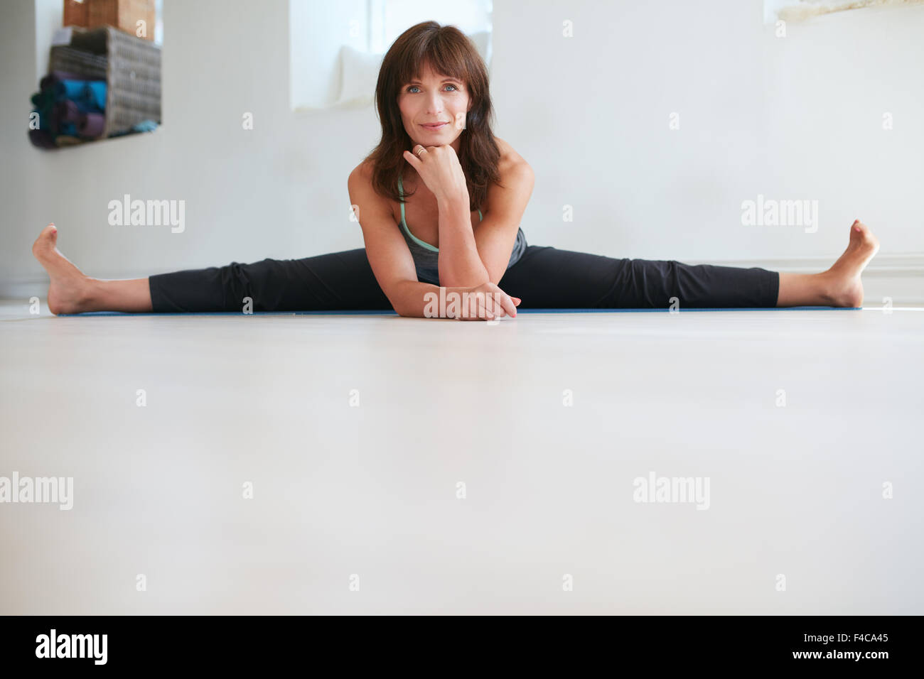 Portrait of flexible woman doing Upavistha Konasana exercise. Female yoga instructor practices yoga at gym. - Stock Image