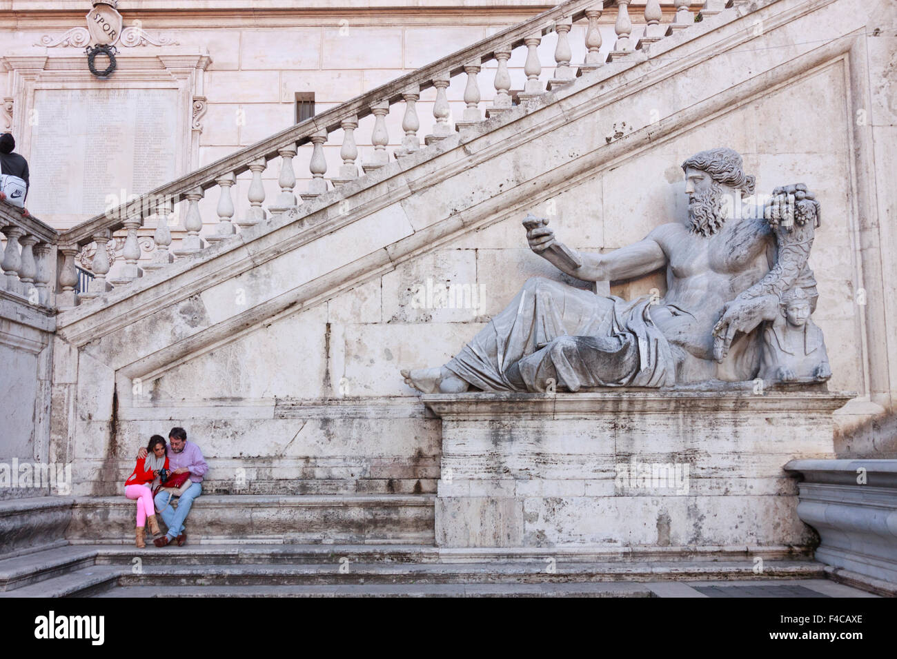 People next to ancient Roman allegory of Nile River by Matteo di Castello on the Senatorial Palace facade on Piazza - Stock Image